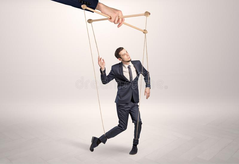 Puppet businessman leaded by a huge hand royalty free stock image
