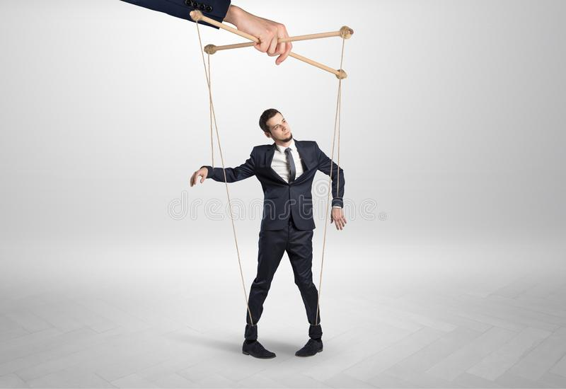 Puppet businessman leaded by a huge hand stock photography