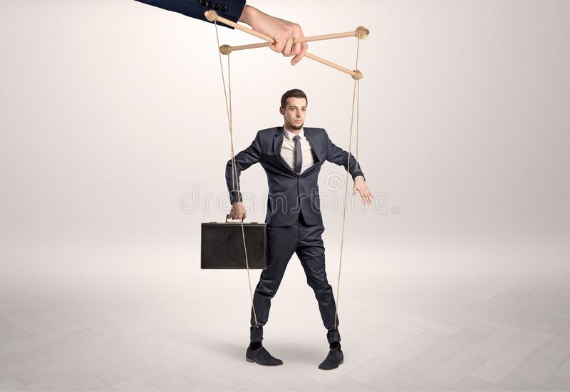 Puppet businessman leaded by a huge hand royalty free stock photo