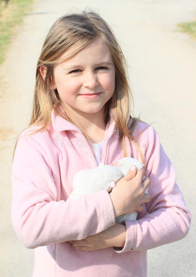 Puppies holded in kids hands. Two white little puppies holded in hands of a smiling little blond girl in pink stock photos