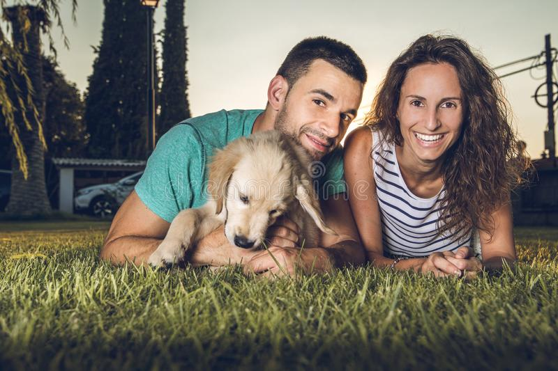 Puppy dog next to a couple of boyfriends. Concept of love between dogs and people stock images