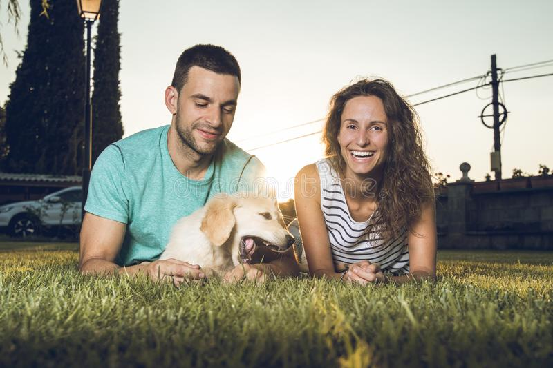 Puppy dog next to a couple of boyfriends. Concept of love between dogs and people stock photo