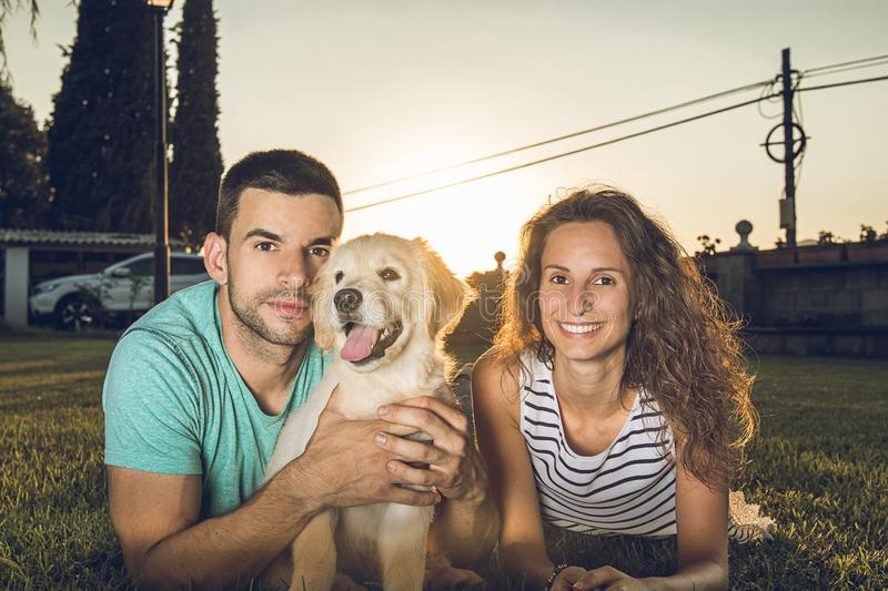 Puppy dog next to a couple of boyfriends. Concept of love between dogs and people stock photography