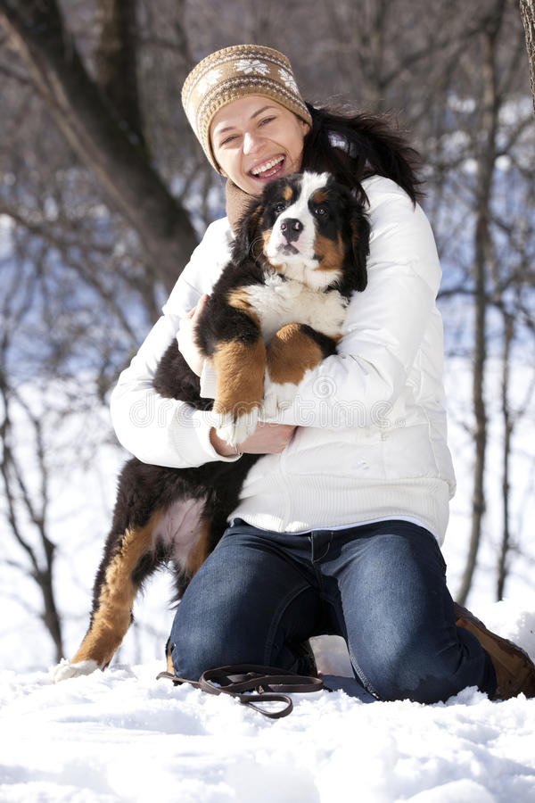 Puppy and girl. Bernese sennenhund puppy and girl against the backdrop of a winter landscape royalty free stock photography