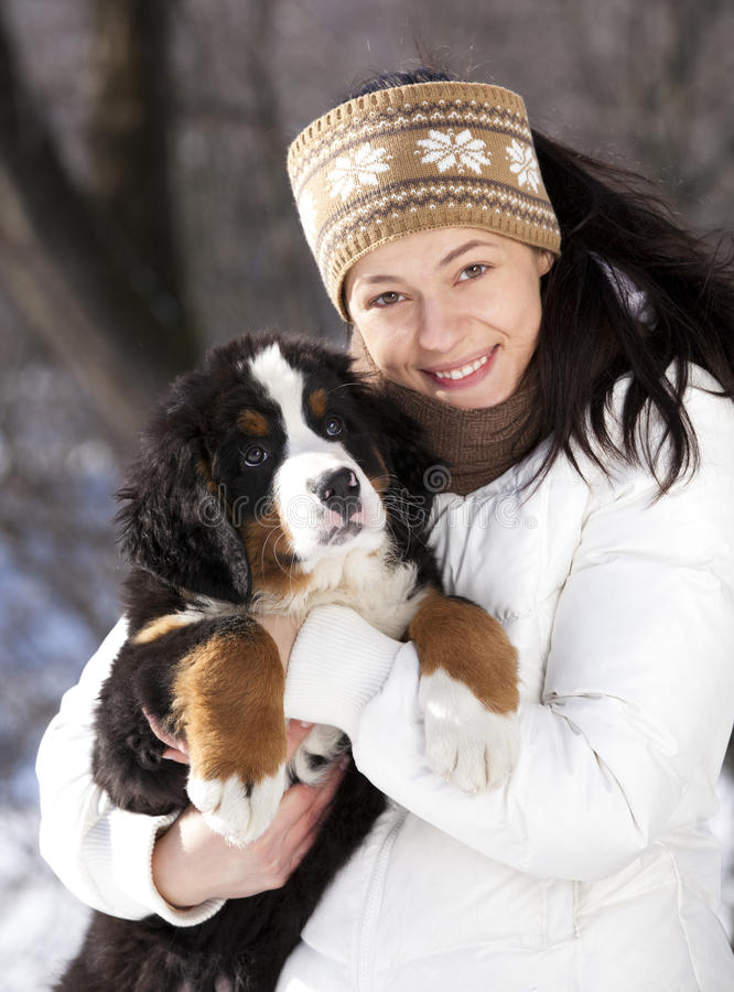 Puppy and girl. Bernese sennenhund puppy and girl against the backdrop of a winter landscape royalty free stock photos