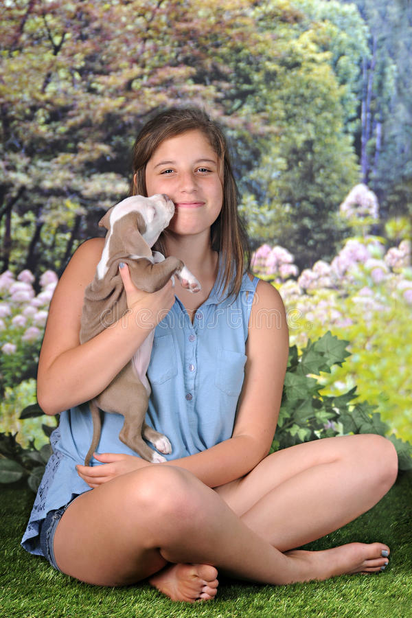 Puppy Kiss. A pretty, barefoot teen girl happily squinting as her new puppy gives her a kiss on a beautiful summer day royalty free stock photography