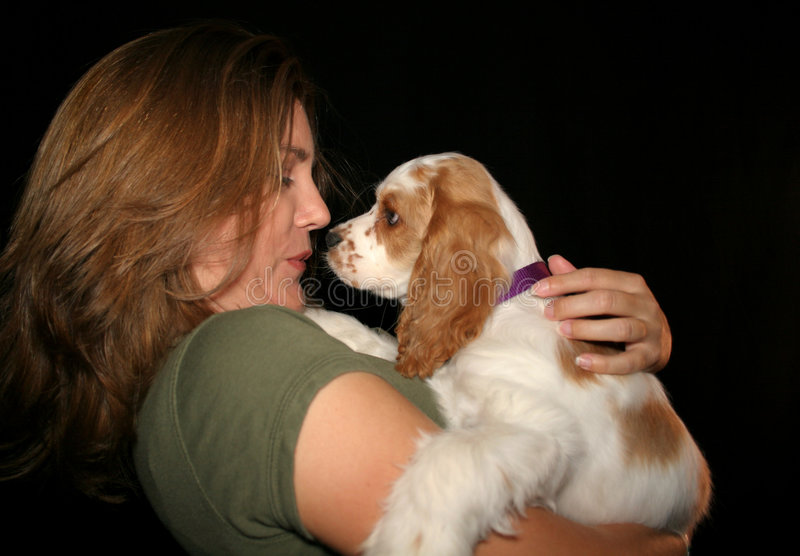 Puppy Kisses. Girl with green shirt kisses puppy nose to nose royalty free stock images