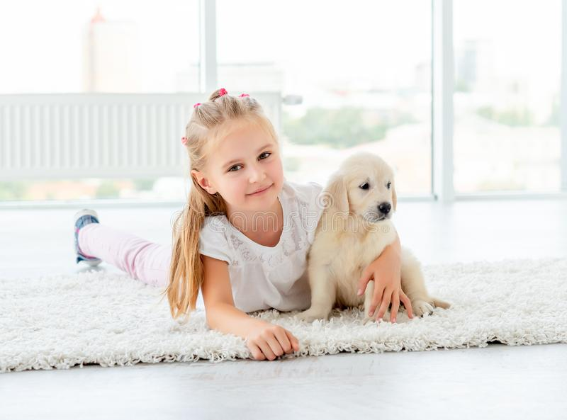 Puppy of retriever and little girl. Indoors lying on carpet royalty free stock photo