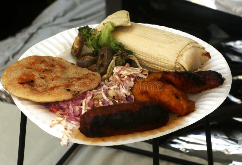 Pupusa med chorizoen, söta pisang, kålsallad och tamales arkivbilder