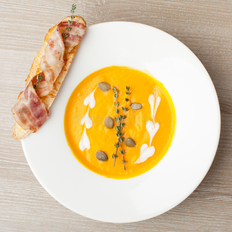 Purée poner crema de la sopa de la calabaza con la rebanada, el tocino y semillas del pan fotos de archivo