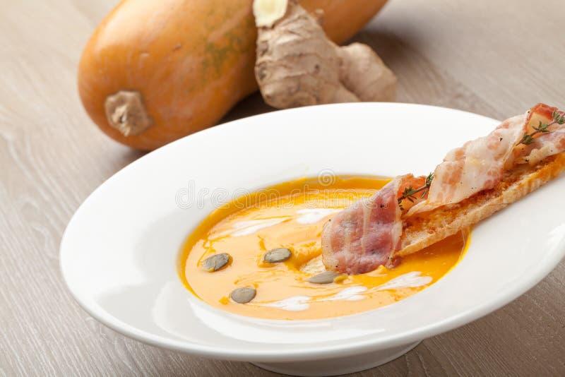Purée poner crema de la sopa de la calabaza con la rebanada, el tocino y semillas del pan imagenes de archivo