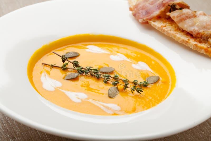 Purée poner crema de la sopa de la calabaza con la rebanada, el tocino y semillas del pan imagen de archivo libre de regalías
