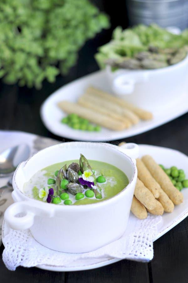 Purè della minestra con i piselli e l'asparago decorato con le viole dei fiori freschi Su un fondo nero in piatti bianchi Pane e fotografia stock libera da diritti