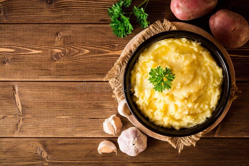 Purè di patate con burro e prezzemolo fresco in ciotola sulla tavola di legno rustica fotografia stock libera da diritti