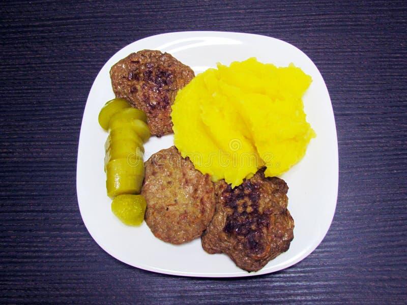 Purè di patate, tortini e cetriolo salato su un piatto immagini stock