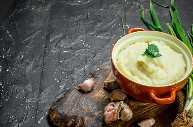 Purè di patate in una ciotola con le cipolle verdi e l'aglio immagini stock libere da diritti