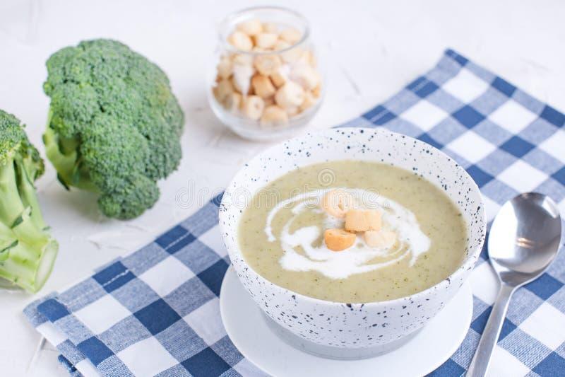 Puré de creme da sopa com brócolis, creme e biscoitos Almoço dos vegetais em um fundo claro Placa e guardanapo na tabela fotos de stock