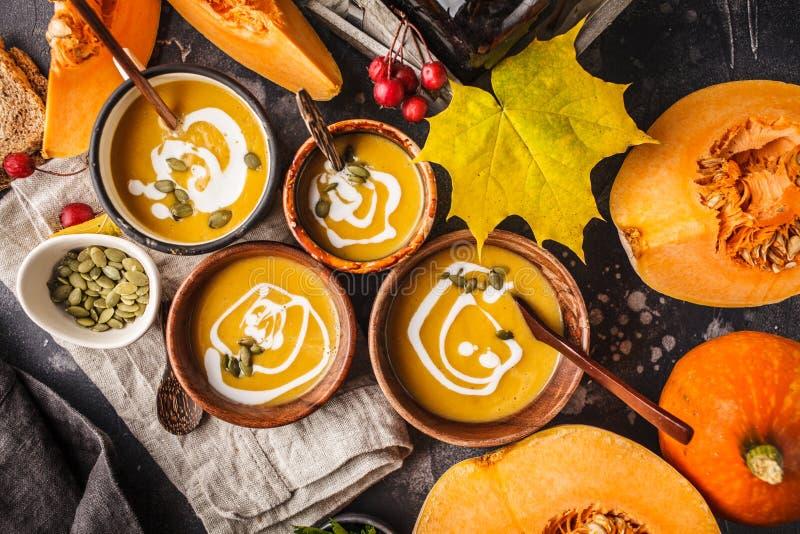 Puré de la sopa de la calabaza de otoño con la crema en tazas, el paisaje del otoño imagen de archivo libre de regalías