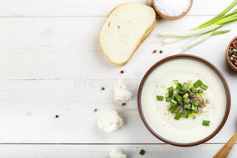 Puré en un fondo blanco, visión superior de la sopa de la coliflor de la patata foto de archivo