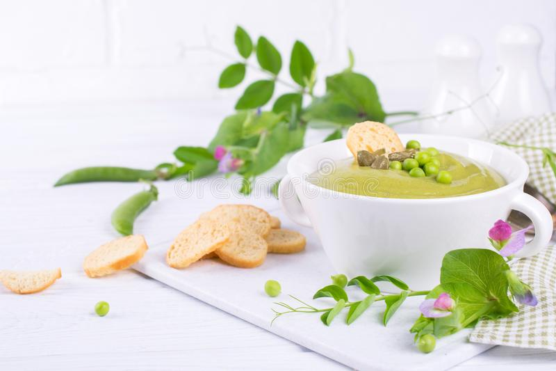 Puré verde de la sopa de guisantes con los cuscurrones en cuenco negro En blanco imagen de archivo