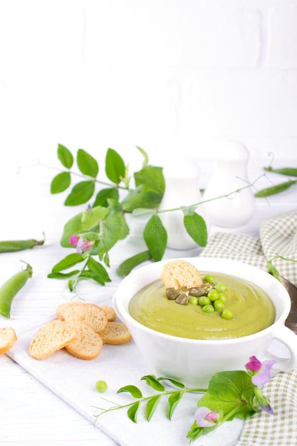 Puré verde de la sopa de guisantes con los cuscurrones en cuenco negro En el fondo blanco foto de archivo libre de regalías