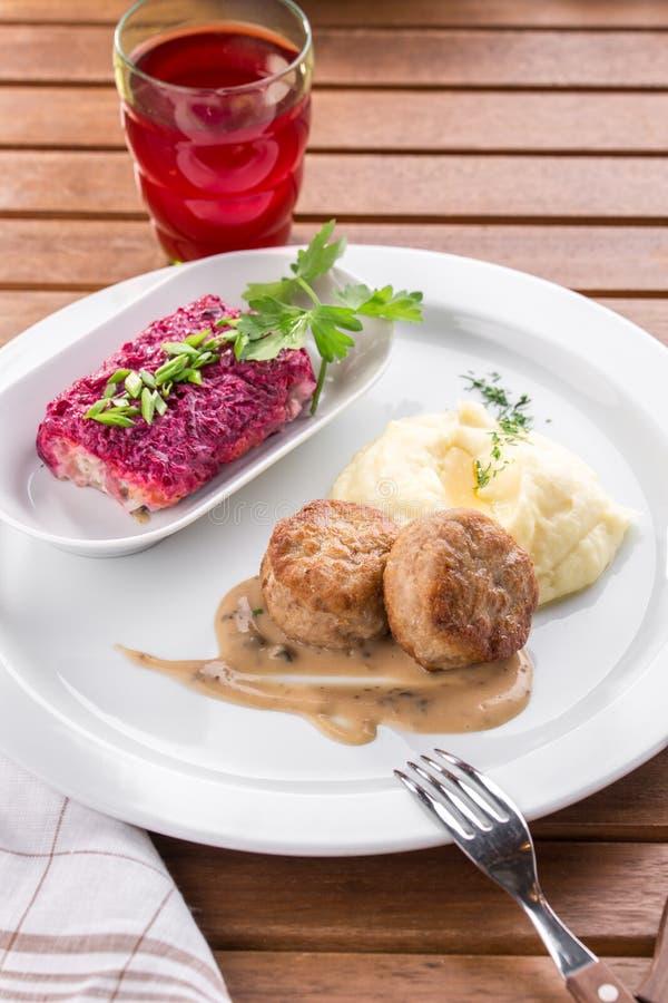 Purée de pommes de terre et boulette de viande et verre de jus sur la table en bois images libres de droits
