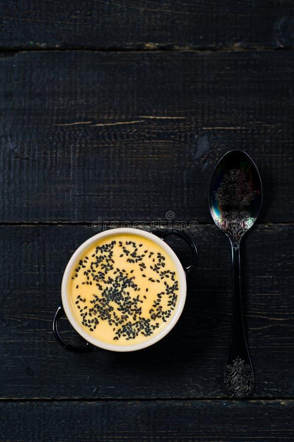 Purée de potiron de soupe avec des graines sur un fond noir photos stock