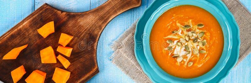 Purée de soupe à potiron dans un plat bleu sur une table bleue en bois Tranches de potiron et de graines de citrouille sur la tab photographie stock libre de droits