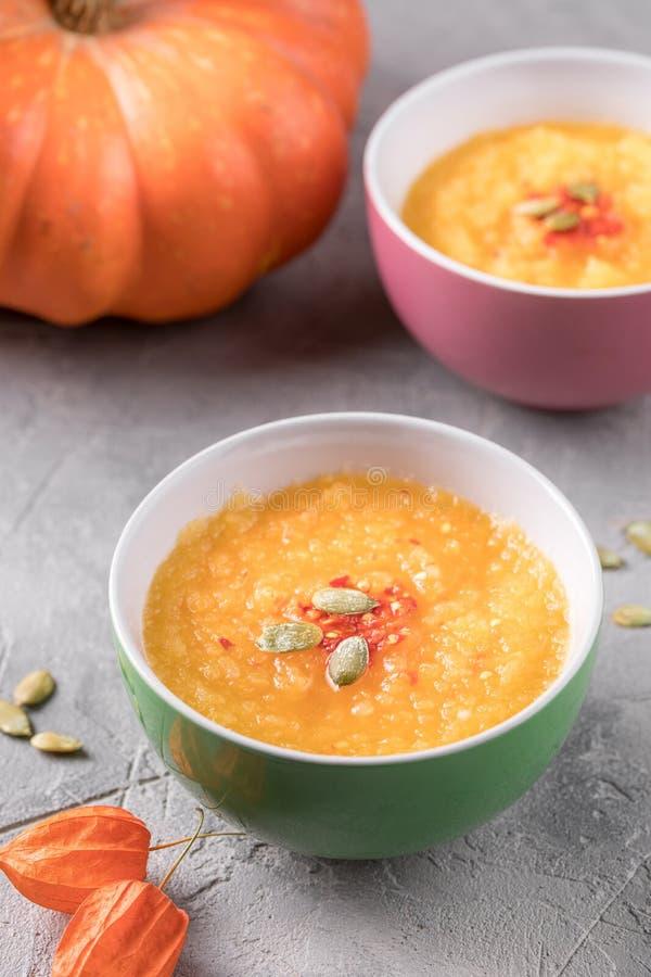 Purée de soupe à potiron en cuvettes en céramique et grand potiron orange sur un fond texturisé gris photos stock
