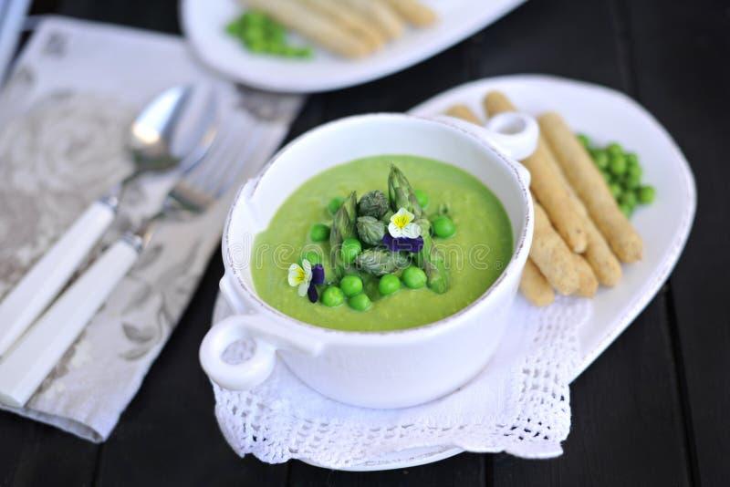 Purée de soupe avec les pois et l'asperge décoré des violettes de fleurs fraîches Sur un fond noir dans les plats blancs Pain et images libres de droits
