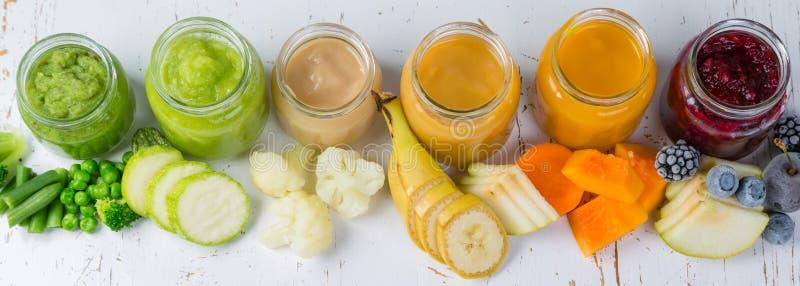 Purés coloridos do comida para bebê nos frascos de vidro imagem de stock