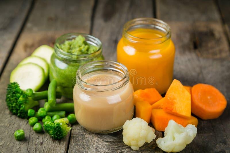Purés coloridos do comida para bebê nos frascos de vidro fotografia de stock