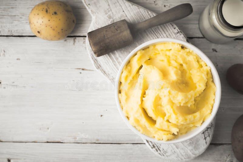 Purés de patata en el cuenco en la tabla de madera blanca con la botella de opinión superior de la leche imagen de archivo libre de regalías