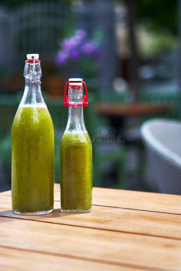 Purés de patata verdes del detox con el kiwi, espinaca bebida en la botella, como la terraza del fondo restonan Copie el espacio fotografía de archivo