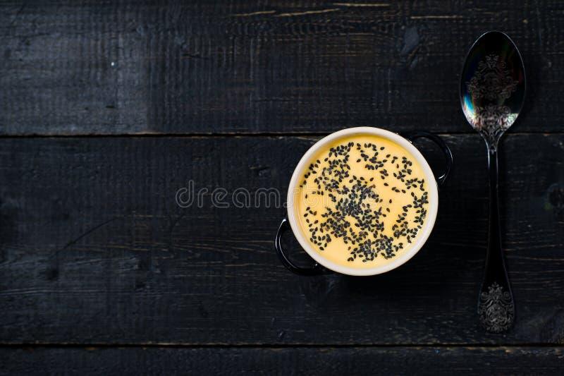 Pur?e de potiron de soupe avec des graines sur un fond noir photographie stock