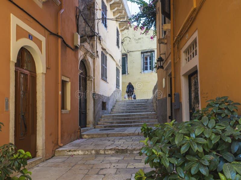 Purchaise de oude de stads smalle straat van Korfu met oudere lokale vrouw het geven zakken met het winkelen, treden, deuren en v royalty-vrije stock fotografie