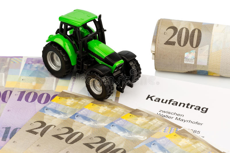 Purchase contract for new farm tractor. The purchase contract for a new tractor at a swiss car dealers. with swiss francs stock photography