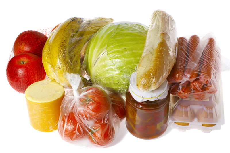 Purchase wrapped raw food isolated. Raw food isolated on white - apples, bananas, cheese, tomatoes, cabbage, bread, sausages, eggs, pot with peppers, all wrapped royalty free stock photo