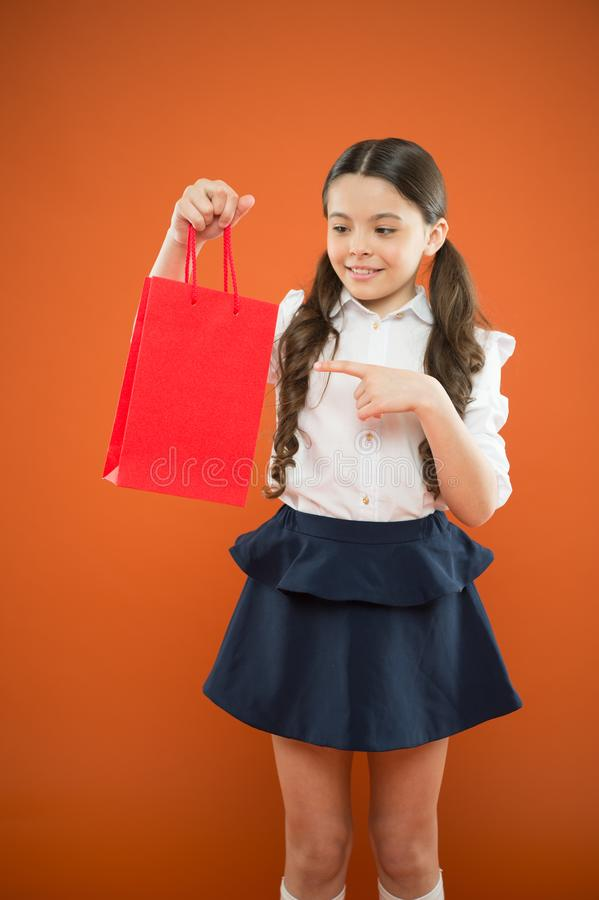 Purchase you need to see. Cute little girl pointing finger at purchase on orange background. Adorable small child. Holding her purchase in red paperbag. Getting royalty free stock image