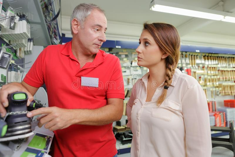 Purchaser woman getting helped by assistant at hardware store stock photo