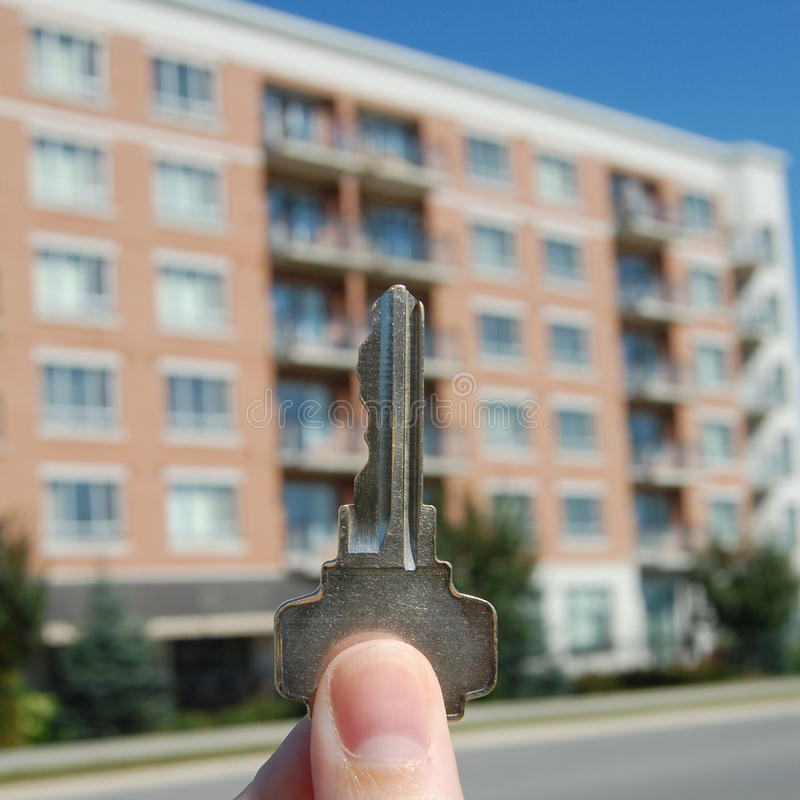 Purchasing an Apartment. A close up of a key in front of an apartment building royalty free stock images