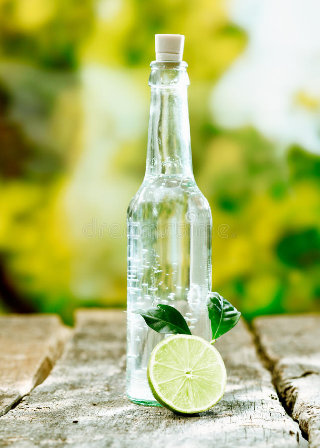 Pure aerated water in a glass bottle. Pure fresh aerated water in a corked glass bottle with sliced lemon on a textured wooden tabletop stock photos