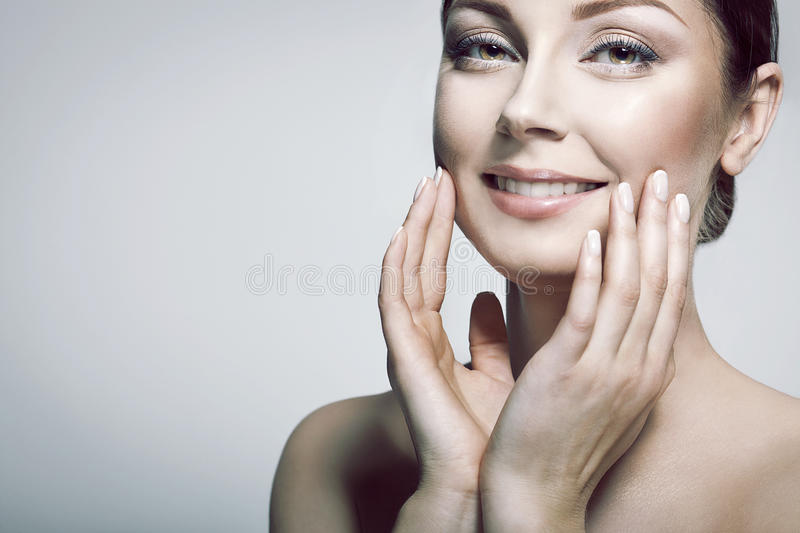 Pure Beautiful Model Girl. Wellbeing and Skin Care Concept . Beauty Portrait. Beautiful Spa Woman Touching her Face. Perfect Fresh Skin. Pure Beautiful Model royalty free stock photography