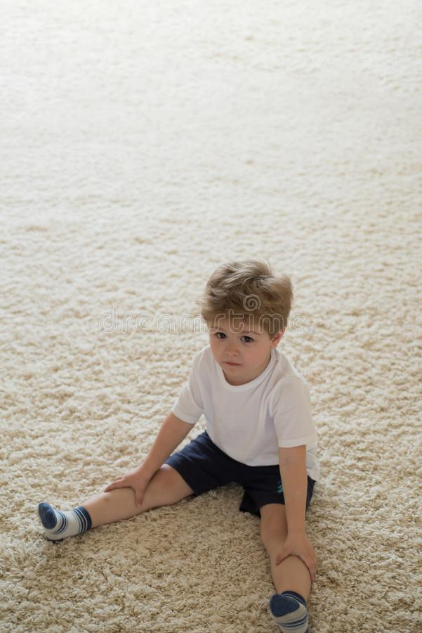 Pure beauty for your hair. Small boy with blond hair sit on floor. Little child with stylish haircut. Little child with. Short haircut. Healthy haircare tips royalty free stock photography