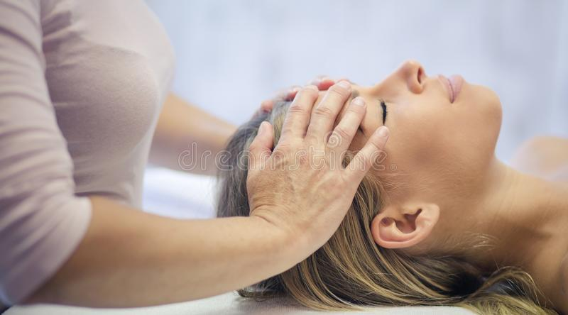 Pure blessing and relaxation. Young adult women enjoying in her relaxing head massage at the spa. Close up. Copy space stock images