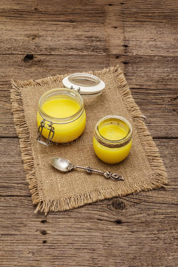 Pure or desi ghee ghi, clarified melted butter. Healthy fats bulletproof diet concept or paleo style plan. Glass jar, silver royalty free stock images