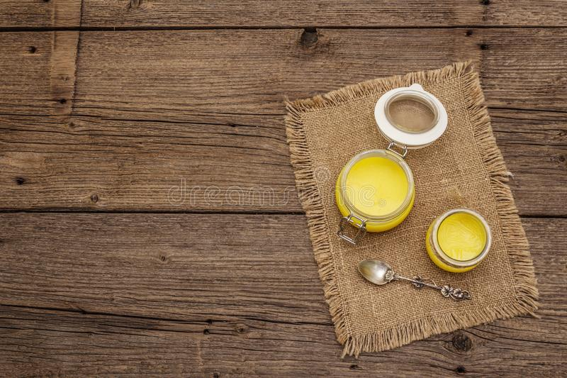 Pure or desi ghee ghi, clarified melted butter. Healthy fats bulletproof diet concept or paleo style plan. Glass jar, silver stock photography