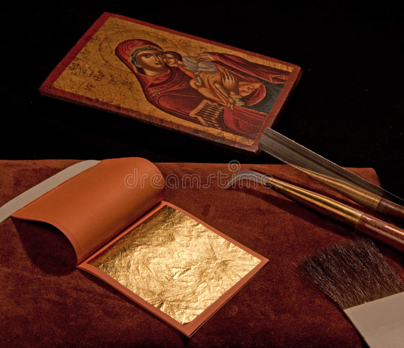 Pure gold leaf with gilding tools and Greek Icon royalty free stock images