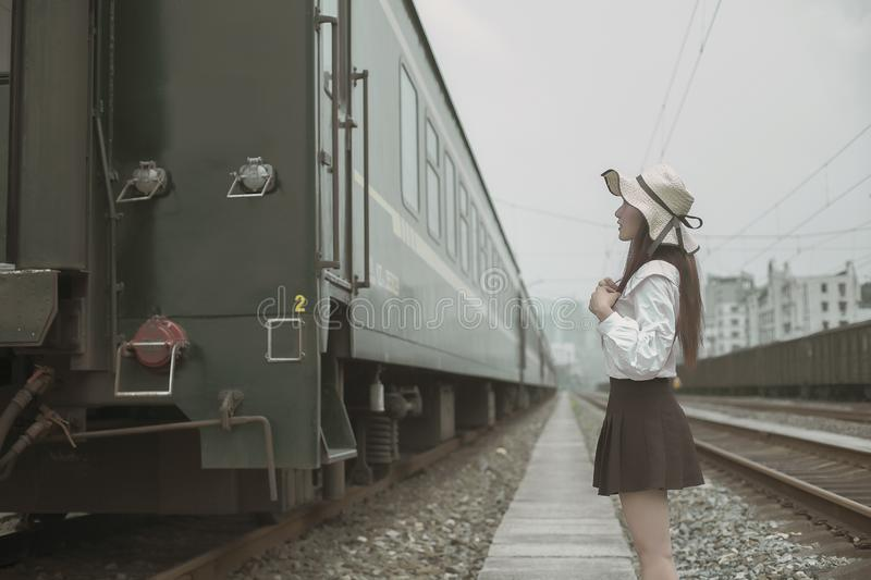 Pure and lovely Asian girl. Pretty lovely girl and rail background. A slightly retro portrait. Play on the rails stock image