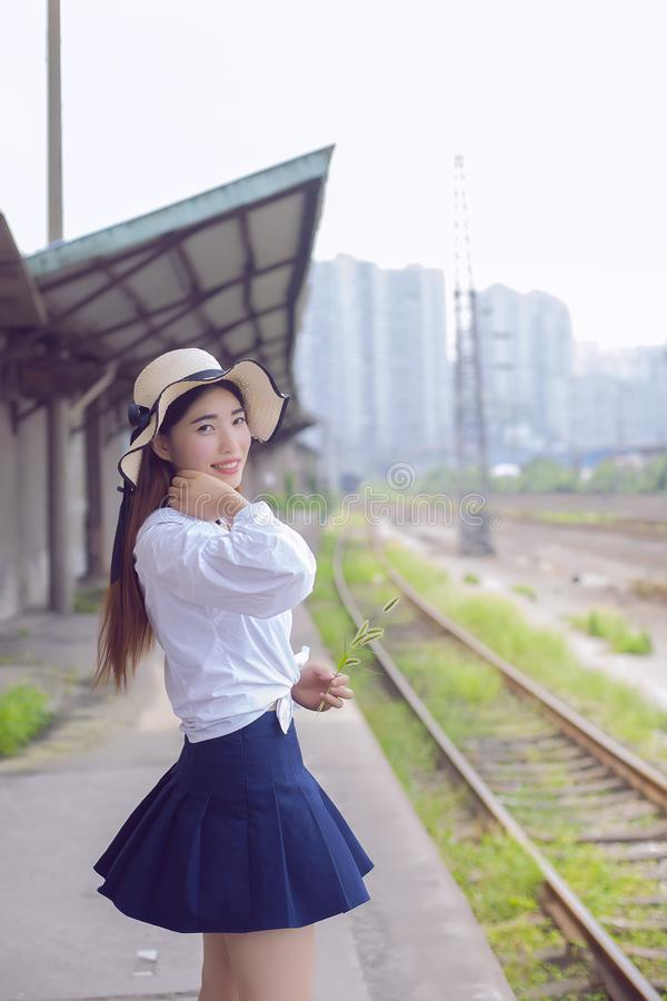Pure and lovely Asian girl. Pretty lovely girl and rail background. She walked on the platform of the train station and smiled back. It was so charming stock photo